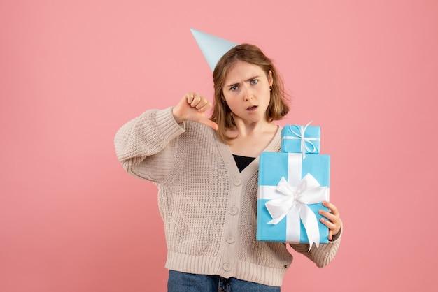 Jonge vrouwelijke bedrijf kerstcadeautjes op roze
