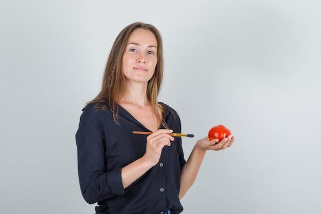 Jonge vrouwelijke bedrijf nep tomaat met borstel in zwart shirt