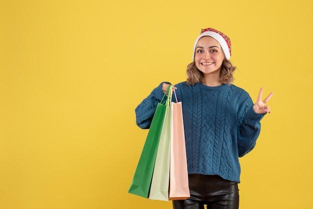 Jonge vrouwelijke bedrijf pakketten na het winkelen op geel
