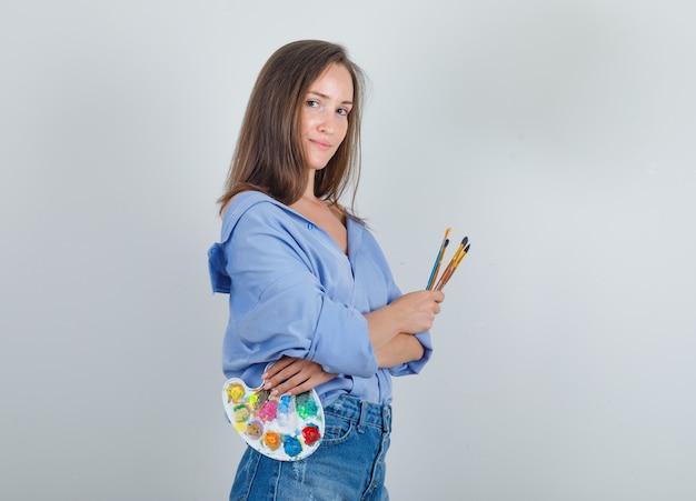 Jonge vrouwelijke bedrijf penselen en palet in shirt, korte broek en op zoek blij