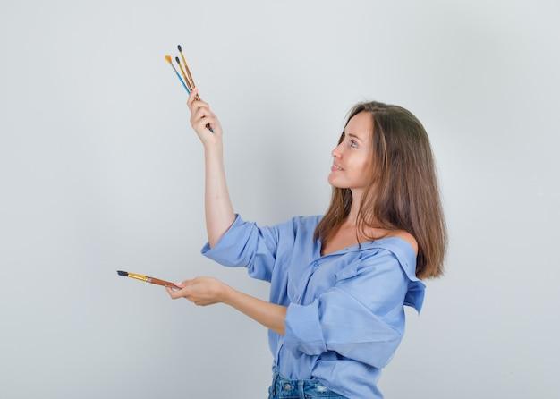 Jonge vrouwelijke bedrijf penselen in shirt, korte broek en op zoek vrolijk