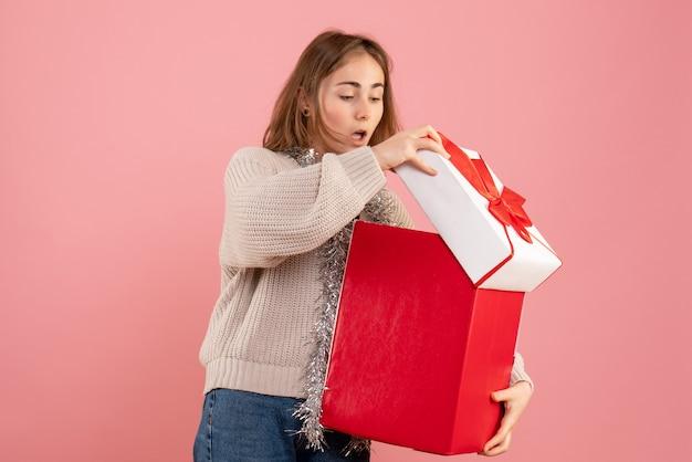 Jonge vrouwelijke bedrijf xmas huidige doos op roze