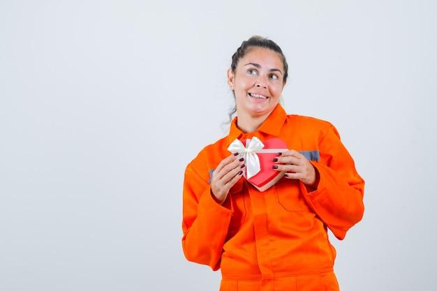 Jonge vrouwelijke bedrijfscadeau in eenvormige werknemer en op zoek vrolijk. vooraanzicht. Gratis Foto