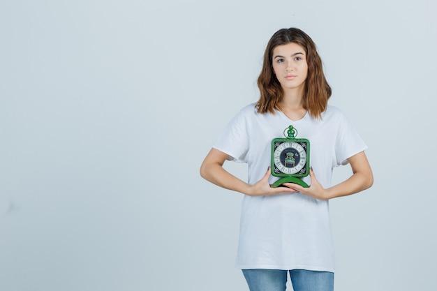 Jonge vrouwelijke bedrijfsklok in wit t-shirt, spijkerbroek en op zoek verstandig. vooraanzicht.