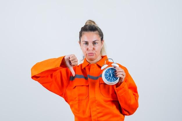 Jonge vrouwelijke bedrijfsklok terwijl duim in arbeidersuniform wordt getoond en ontevreden kijkt. vooraanzicht.