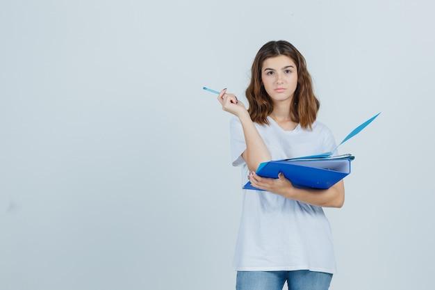 Jonge vrouwelijke bedrijfsmappen en pen in wit t-shirt, spijkerbroek en op zoek peinzend, vooraanzicht.