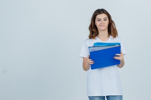 Jonge vrouwelijke bedrijfsmappen in wit t-shirt, spijkerbroek en op zoek peinzend, vooraanzicht.