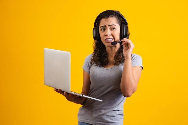 Jonge vrouwelijke begeleider die klachten van klanten ontvangt in telemarketing.