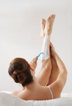 Jonge vrouwelijke benen scheren met een scheermesje liggend op bed