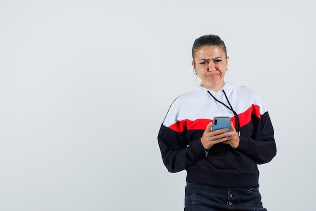 Jonge vrouwelijke bericht aan het typen aan iemand in kleurrijke sweatshirt en peinzend, vooraanzicht op zoek.