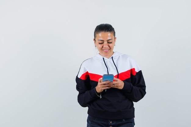 Jonge vrouwelijke bericht aan het typen op telefoon in kleurrijke sweater en op zoek gericht. vooraanzicht.