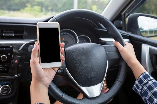 Jonge vrouwelijke bestuurder die smartphone van het aanrakingsscherm en het stuurwiel van de handholding in een auto gebruiken.
