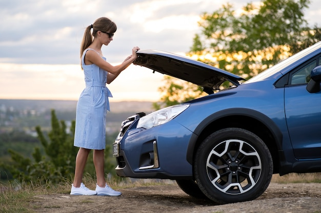 Jonge vrouwelijke bestuurder die zich dichtbij een kapotte auto bevindt met open kap die haar voertuigmotor inspecteert en op hulp wacht.