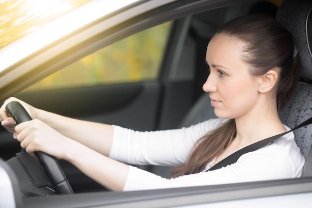 Jonge vrouwelijke bestuurder kijkend naar de zijuitkijkspiegels