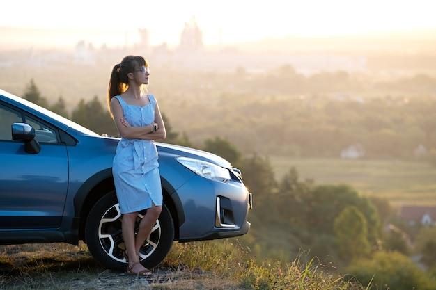 Jonge vrouwelijke bestuurder rusten in de buurt van haar auto genieten van warme zomeravond. reis- en ontsnappingsconcept.