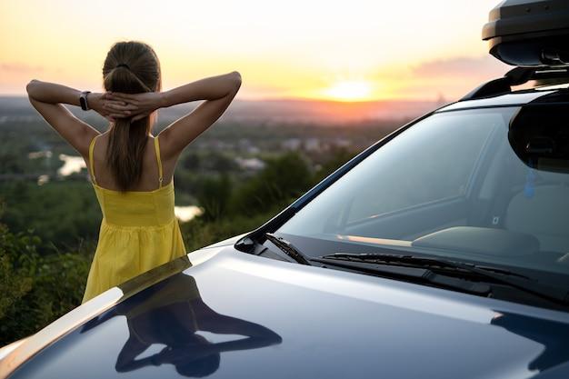 Jonge vrouwelijke bestuurder rusten in de buurt van haar auto op warme zomeravond