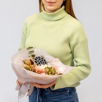 Jonge vrouwelijke bloemist die een boeket van bloemen houdt