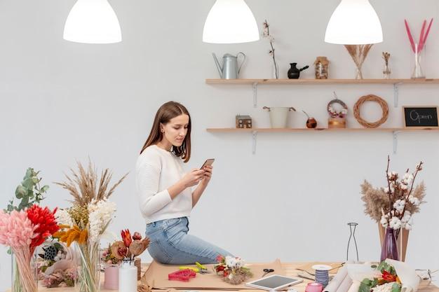 Jonge vrouwelijke bloemist die haar mobiele telefoon met behulp van