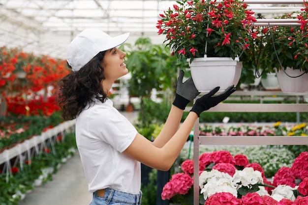 Jonge vrouwelijke bloemist die voor planten zorgt in de kas