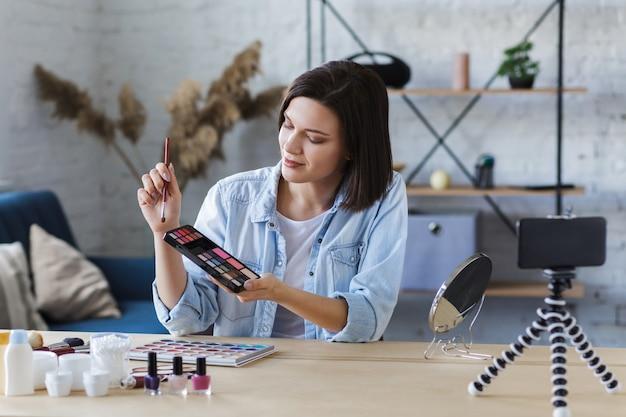 Jonge vrouwelijke blogger die een instructievideo opneemt voor haar beautyblog over cosmetica