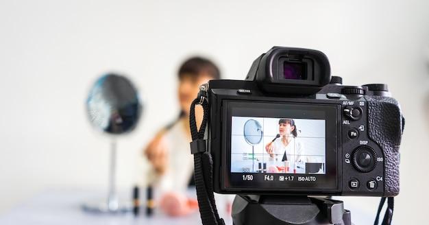 Jonge vrouwelijke blogger die vlog video op het camerascherm thuis bekijkt en opneemt met make-upschoonheidsmiddel thuis. focus op het camerascherm.
