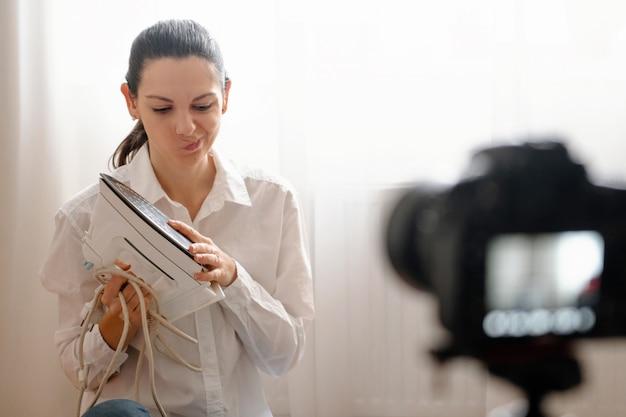 Jonge vrouwelijke blogger met camera dslr vlogging verwerkt huishoudelijk product in fles moderne online werk concept