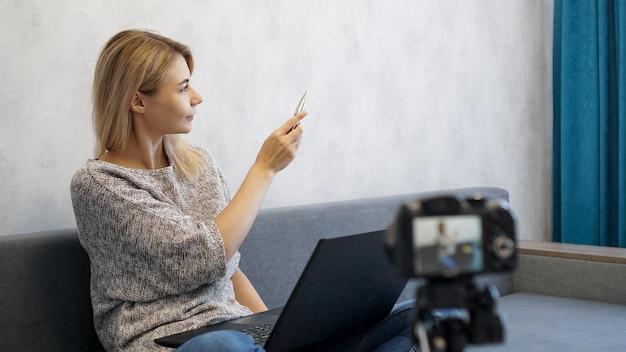 Jonge vrouwelijke blogger met laptop en pen. ze praat over zaken of neemt een lezing op.