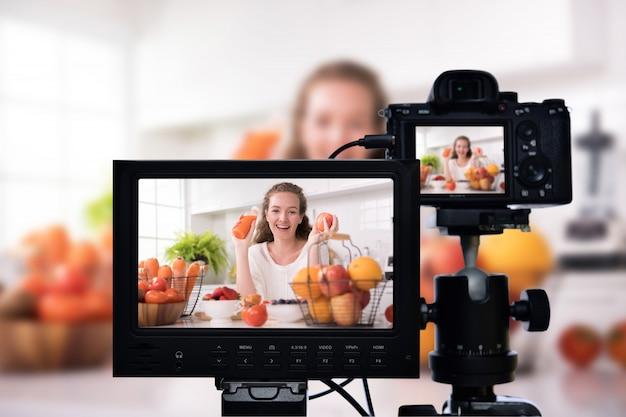Jonge vrouwelijke blogger vlogger en online influencer die videocontent over gezonde voeding opneemt