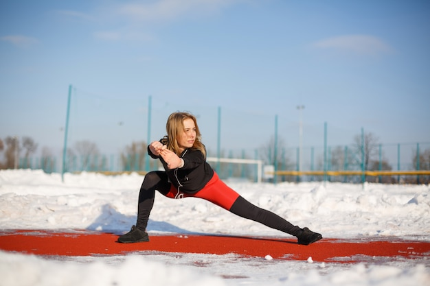 Jonge vrouwelijke blonde in violette beenkappen die oefening op een rode renbaan in een sneeuwstadion uitrekken.