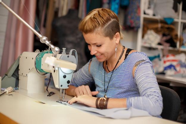 Jonge vrouwelijke blonde naaister werkt op naaimachine.