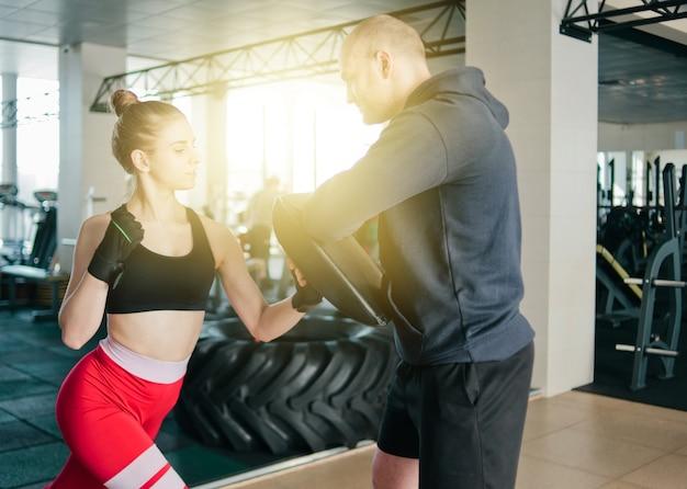 Jonge vrouwelijke boksen op sportschool met mannelijke instructeur. paar dat ponsen uitoefent