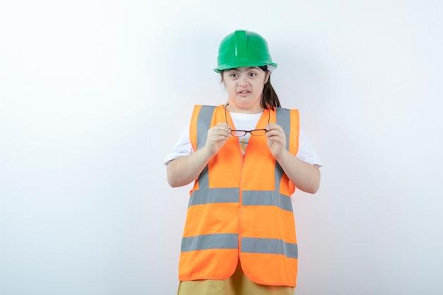 Jonge vrouwelijke bouwvakker die haar bril over witte muur draagt