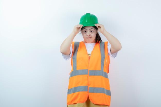 Jonge vrouwelijke bouwvakker die haar groene helm over witte muur draagt