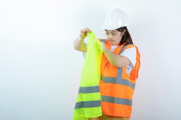 Jonge vrouwelijke bouwvakker in bouwvakker die vest over witte muur draagt.