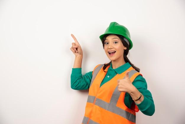 Jonge vrouwelijke bouwvakker op witte achtergrond.