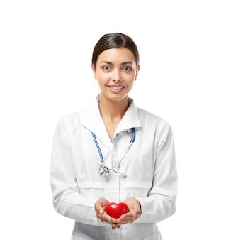 Jonge vrouwelijke cardioloog die plastic hart houdt dat op wit wordt geïsoleerd