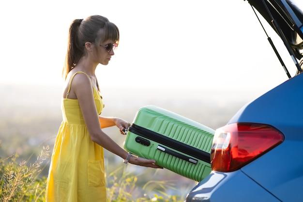 Jonge vrouwelijke chauffeur die groene koffer uit de kofferbak haalt. reizen en vakanties concept.