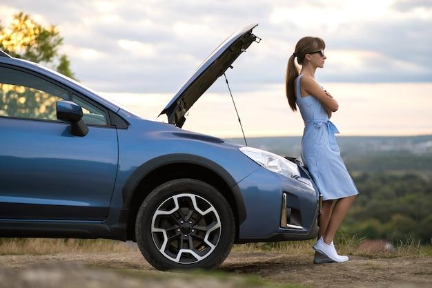 Jonge vrouwelijke chauffeur die in de buurt van een kapotte auto staat met een opgeklapte motorkap, wachtend op hulp.