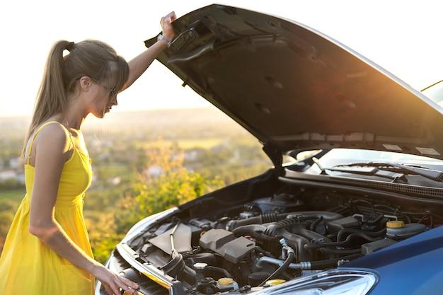Jonge vrouwelijke chauffeur die in de buurt van haar auto staat met een gesprongen kap met motorproblemen.