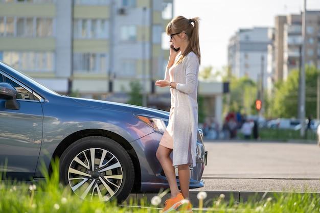 Jonge vrouwelijke chauffeur die in de zomer in de buurt van haar auto staat en op een mobiele telefoon praat