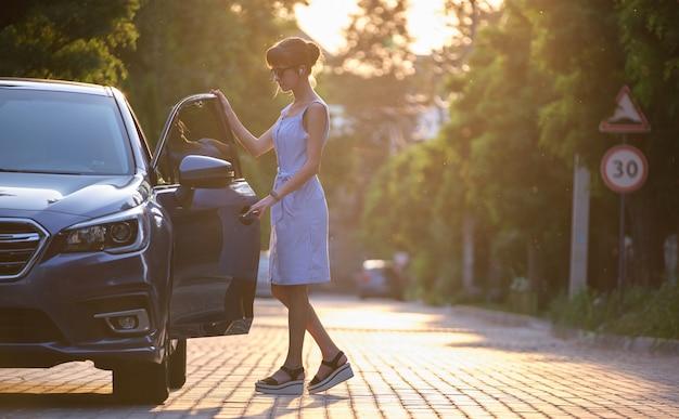 Jonge vrouwelijke chauffeur die in haar auto stapt. vervoer en verkeer concept.
