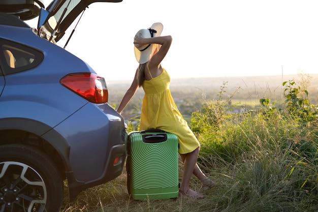 Jonge vrouwelijke chauffeur die rust heeft op een koffer in de buurt van haar auto in het zomerveld. reizen en vakanties concept.