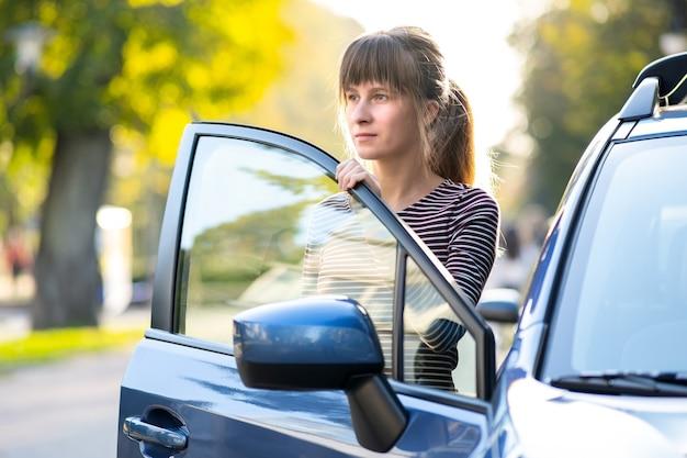 Jonge vrouwelijke chauffeur geniet van een warme zomerdag naast haar auto op straat in de stad. reizen en vakantie concept.