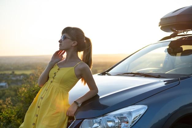 Jonge vrouwelijke chauffeur rust in de buurt van haar auto op warme zomerdag.