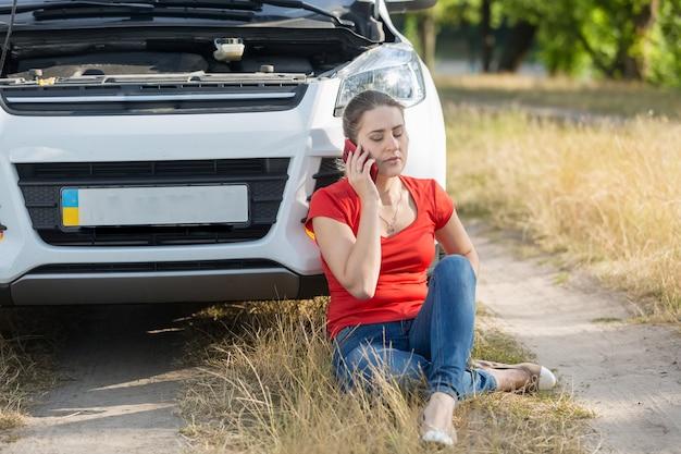 Jonge vrouwelijke chauffeur zittend op de grond naast een kapotte auto en om hulp roepend