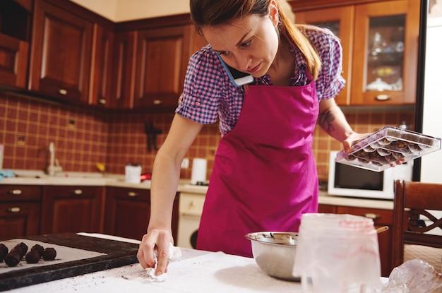 Jonge vrouwelijke chef-kok chocolatier praten op mobiele telefoon tijdens de productie van handgemaakte chocolade snoepjes