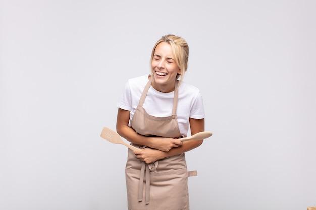 Jonge vrouwelijke chef-kok die hardop lacht om een of andere hilarische grap, zich gelukkig en opgewekt voelt, plezier heeft