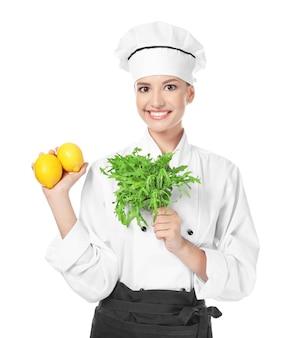 Jonge vrouwelijke chef-kok met rucola en citroenen op wit