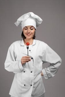 Jonge vrouwelijke chef-kok met tomaat op fork