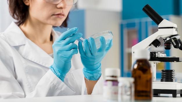 Jonge vrouwelijke chemicus en microscoop